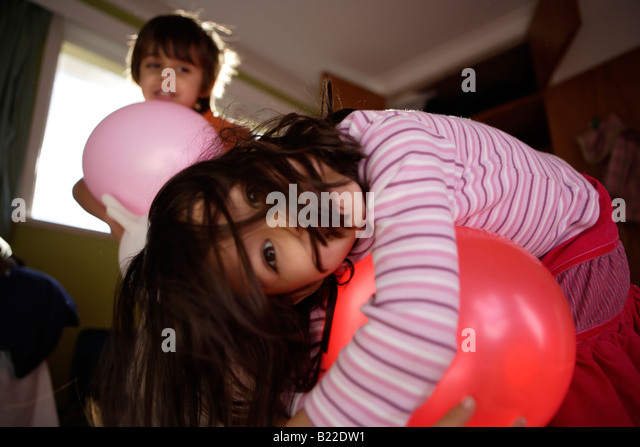 Boy aged six and sister aged four play with balloons in their bedroom. Mixed race asian english - Stock Image