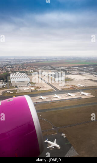 Cropped view of pink aeroplane fuselage of aircraft flying above Belgium. - Stock Image