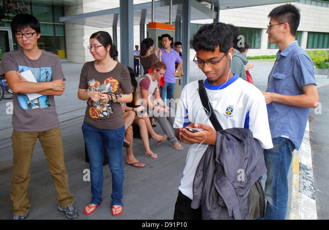 Singapore National University of Singapore NUS University Town school student campus Asian woman man texting using - Stock Image