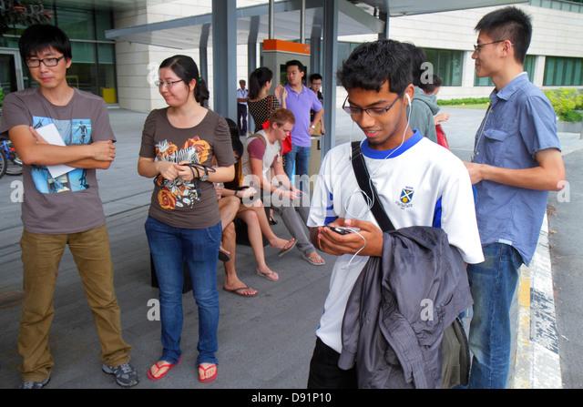Singapore National University of Singapore NUS University Town school student campus Asian woman man texting using - Stock Image