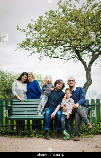 Portrait of homosexual families at park - Stock-Bilder