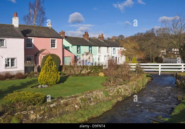 Pastel coloured cottages alongside the beck in Calthwaite, John Peel Country, Cumbria, England, UK - Stock Image