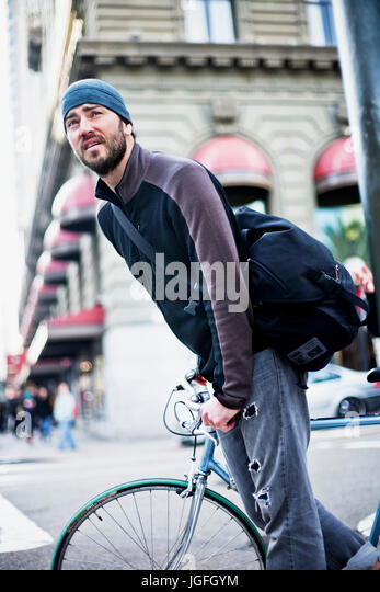 Caucasian man riding bicycle in city - Stock Image