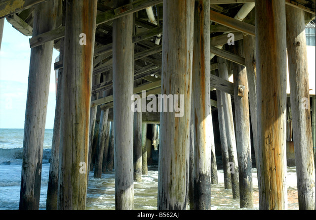 The poles supporting the pier on Daytona Beach, Florida - Stock Image