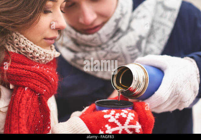 Young guy pouring hot tea for his girlfriend - Stock Image