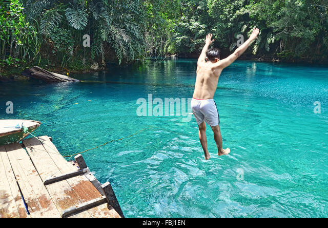 A boy jumping into Labuan Cermin Lake - Stock Image