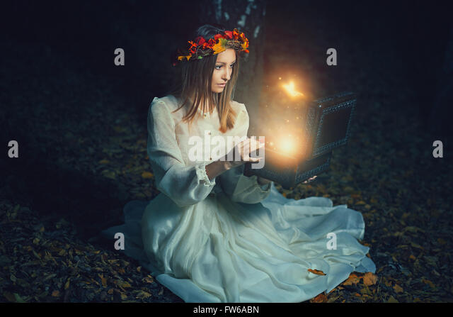 Beautiful woman opens a magical box full of fairies . Fantasy concept - Stock-Bilder
