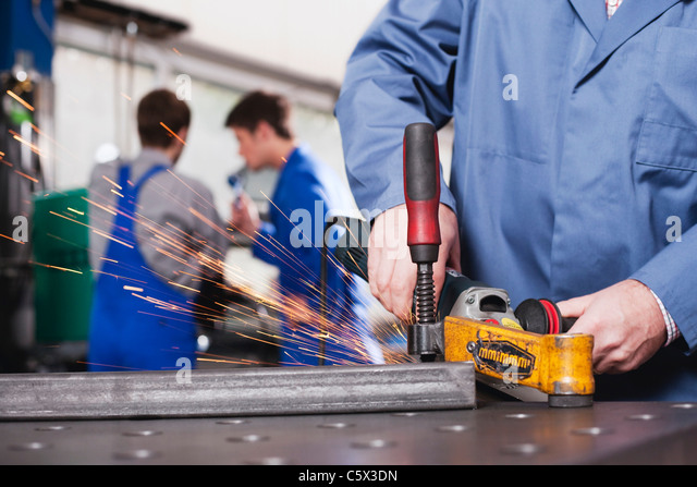 Germany, Neukirch, Person using grinder,  Apprentice and foreman in background - Stock-Bilder