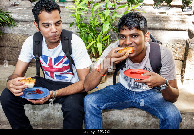 India Asian Mumbai Fort Mumbai Kala Ghoda Mahatma Gandhi Road man friends eating street food - Stock Image