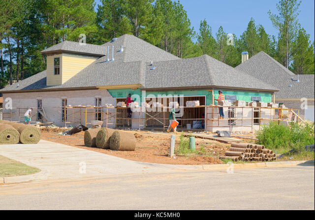 Brick layers working on a new home under construction need to use scaffolding to reach the upper parts of the exterior - Stock Image