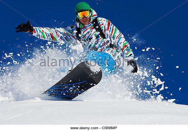 A snowboarder riding fast through fresh powder snow. - Stock-Bilder