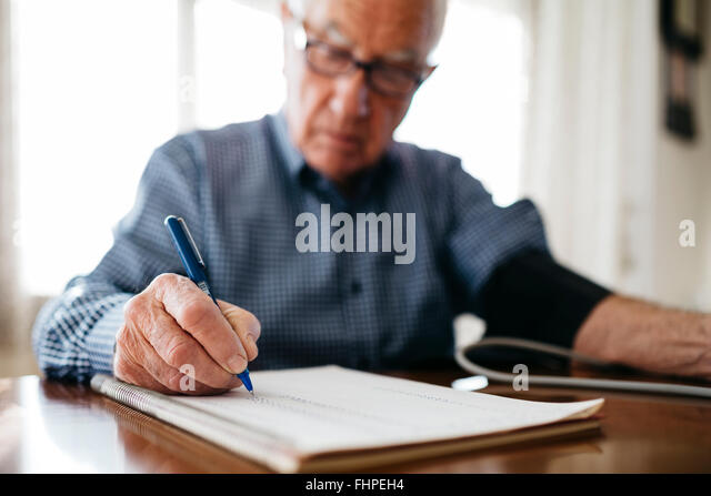 Senior man controlling his blood pressure and writing down the result, close-up - Stock Image