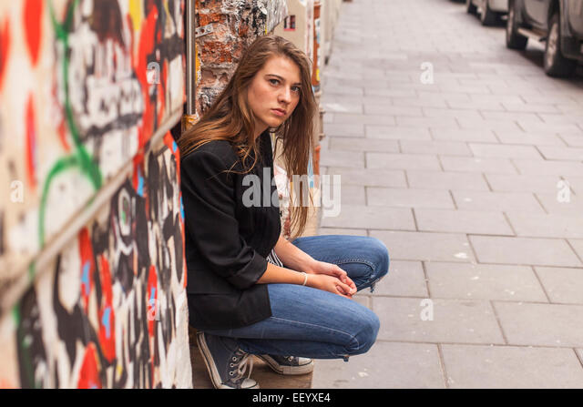 Hipster girl sitting on the street. - Stock Image