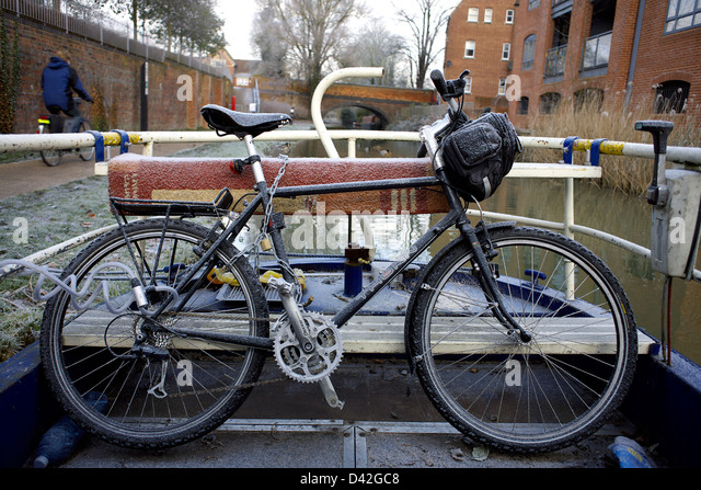 Bicycle on a narrowboat on the South Oxford Canal in winter snow ice cyclist cycle cycling bike City of Oxford Oxfordshire - Stock Image