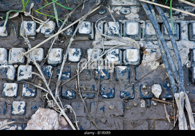 Computer keyboard covered in mud - Stock Image