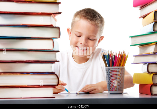 Portrait of cute youngster sitting among stacks of literature and drawing - Stock Image