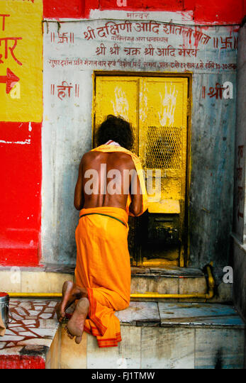 Man praying in front of a temple in Varanasi, India - Architecture and daily street life - Stock Image