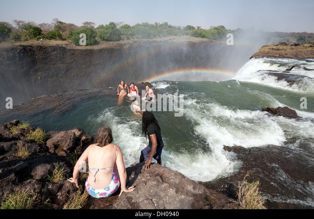 People swimming in Devils Pool at the edge of the Victoria Falls, Adventure travel in Zambia Africa - Stock-Bilder