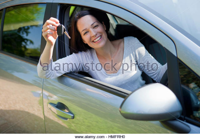 Portrait happy woman in new car holding keys - Stock-Bilder