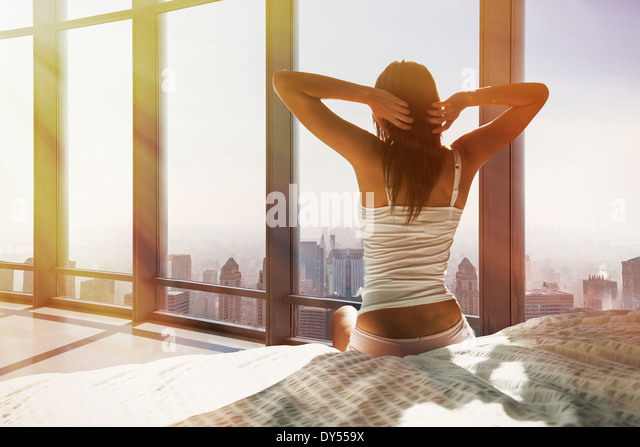 Young woman sitting on bed, stretching, overlooking city - Stock-Bilder