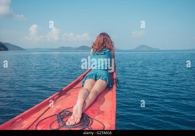 A young woman is relaxing on the bow of a small boat in a tropical climate - Stock Image