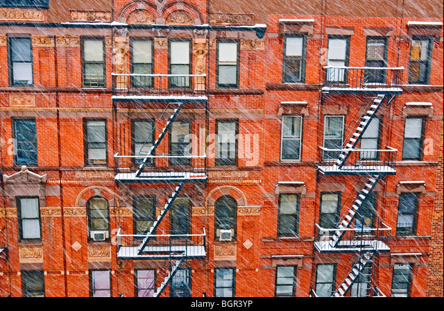 Tenement apartment buildings in New York City during winter snowstorm. - Stock Image