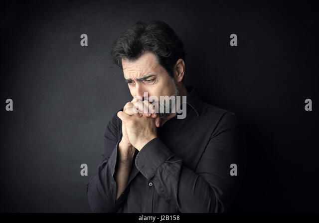 Sad man in black crying - Stock Image