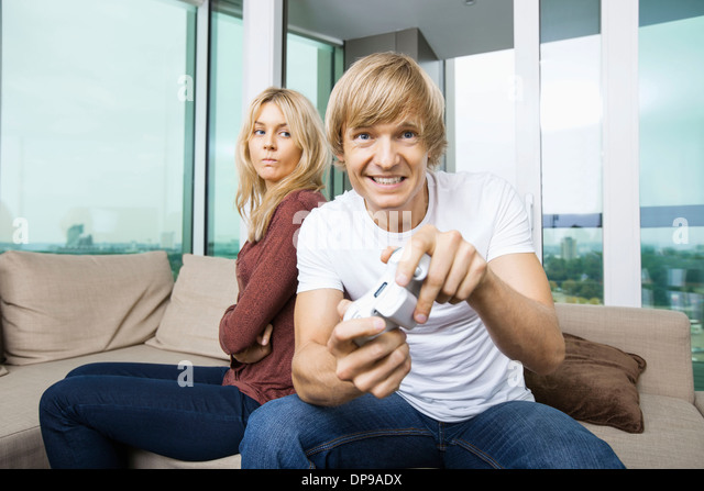 Angry woman looking at man play video game in living room at home - Stock Image