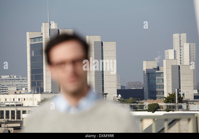 Defocused portrait of man in front of hifg-rise buildings - Stock Image