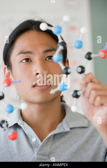 Asian male college student looking at molecule model - Stock Image