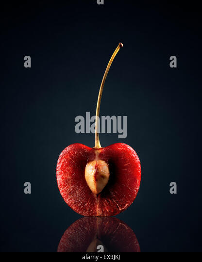 Red Cherry (halved) with reflection on dark background - Stock Image