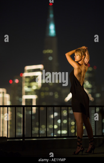 A young woman standing on a rooftop overlooking a brightly lit city skyline. - Stock Image