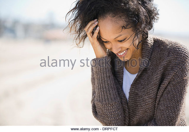 Shy woman standing on beach - Stock Image