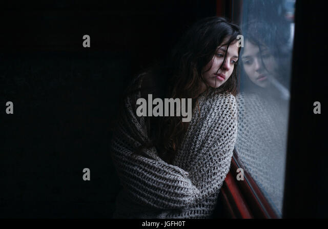 Sad Caucasian woman wrapped in scarf leaning on window - Stock Image