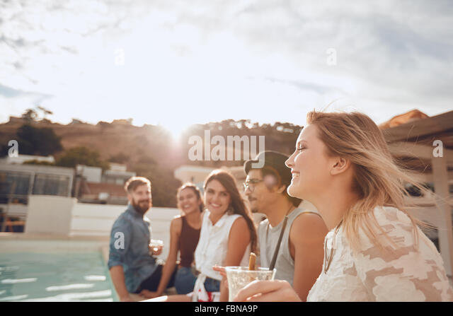 Group of friends sitting in a row on the edge of swimming pool and enjoying party. Cheerful young people having - Stock Image