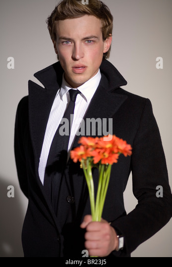 A male model holding flowers during a photo shoot at a studio in Los Angeles, USA. - Stock Image