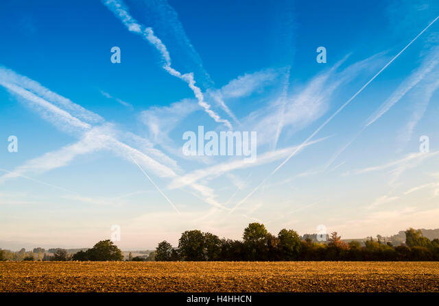 Blue skyscape with contrails or chemtrails - France. - Stock Image