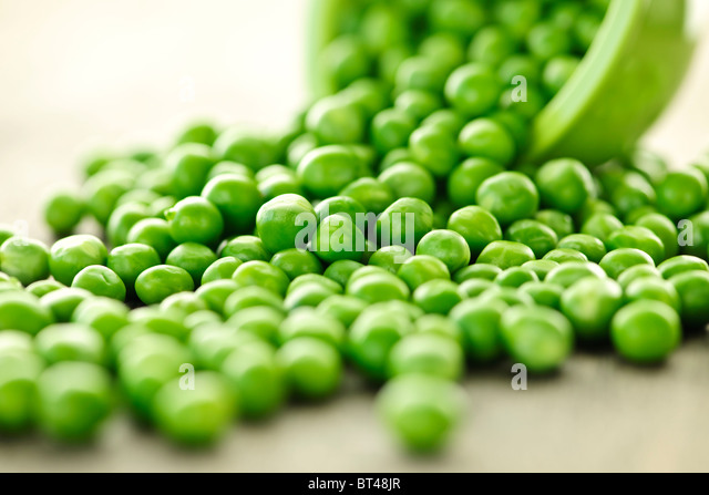Closeup on spilling bowl of fresh green green peas - Stock Image