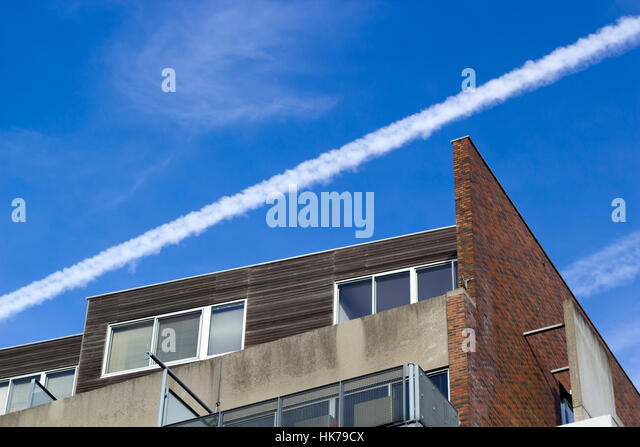 Amsterdam, the Netherlands - January 20, 2017: Aircraft vapour trail over an apartment block - Stock Image