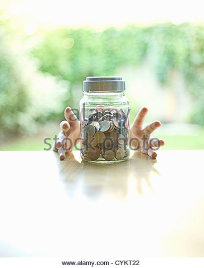Hands grabbing jar of change - Stock Image