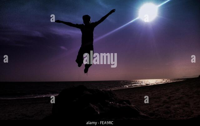 Silhouette Man Jumping At Beach Against Bright Sun - Stock Image