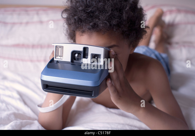 Liitle boy holding instant camera - Stock Image