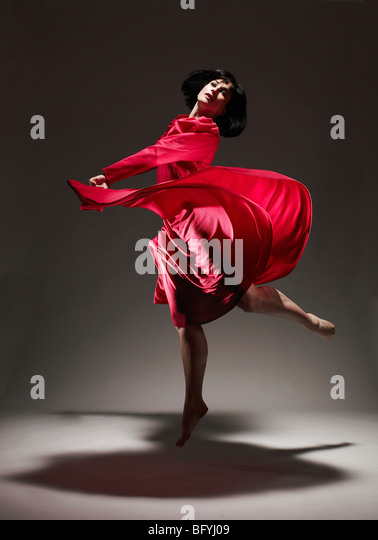 Woman in Red dress dancing under light - Stock Image