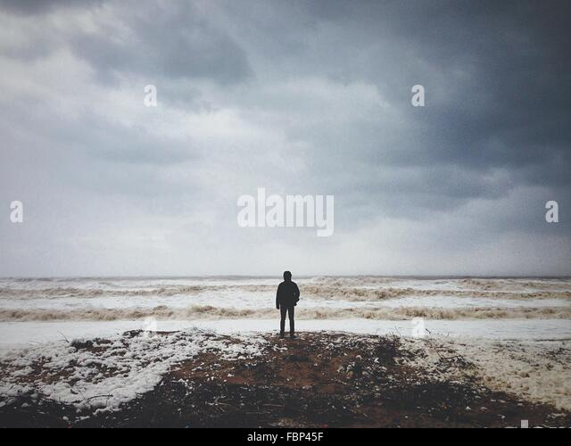 Man Standing On Beach Against Cloudy Sky - Stock Image