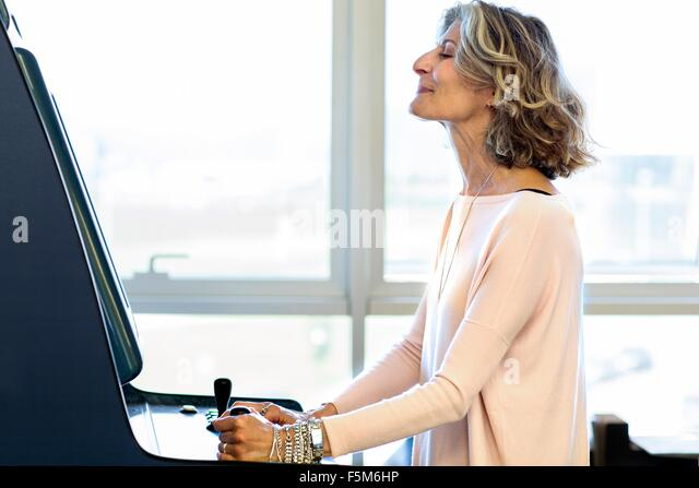 Senior female designer playing on games machine in office - Stock Image