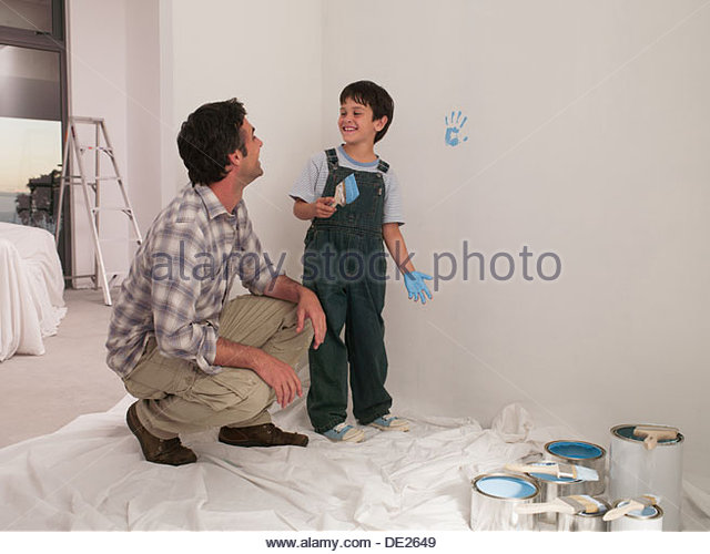 Father watching son make handprint on wall with paint - Stock Image