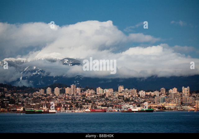 Barges in Burrard Inlet and the North Shore Mountains North Vancouver British Columbia Canada - Stock Image
