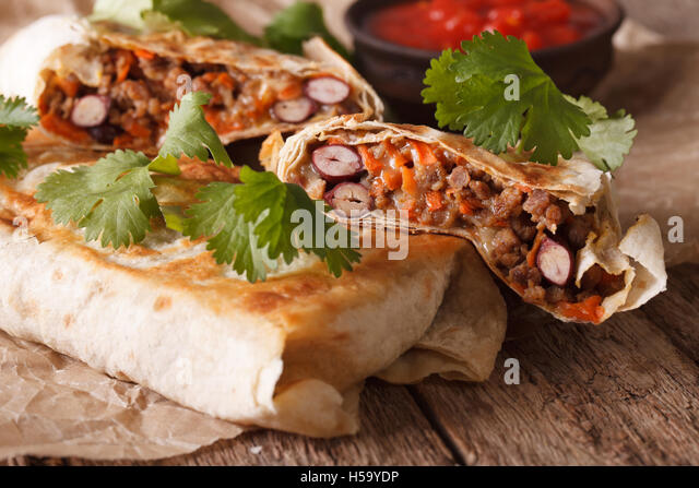 chimichanga with ground meat, beans and cheese macro on the table. Horizontal - Stock Image