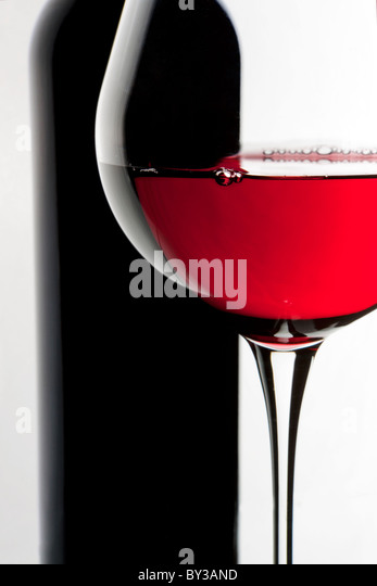Still-life with bottle and glass of red wine over white background. - Stock-Bilder