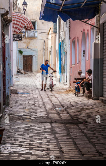 Young man walks his moped down a narrow cobbled sidestreet in the Medina in Sousse,Tunisia while two others chat - Stock-Bilder